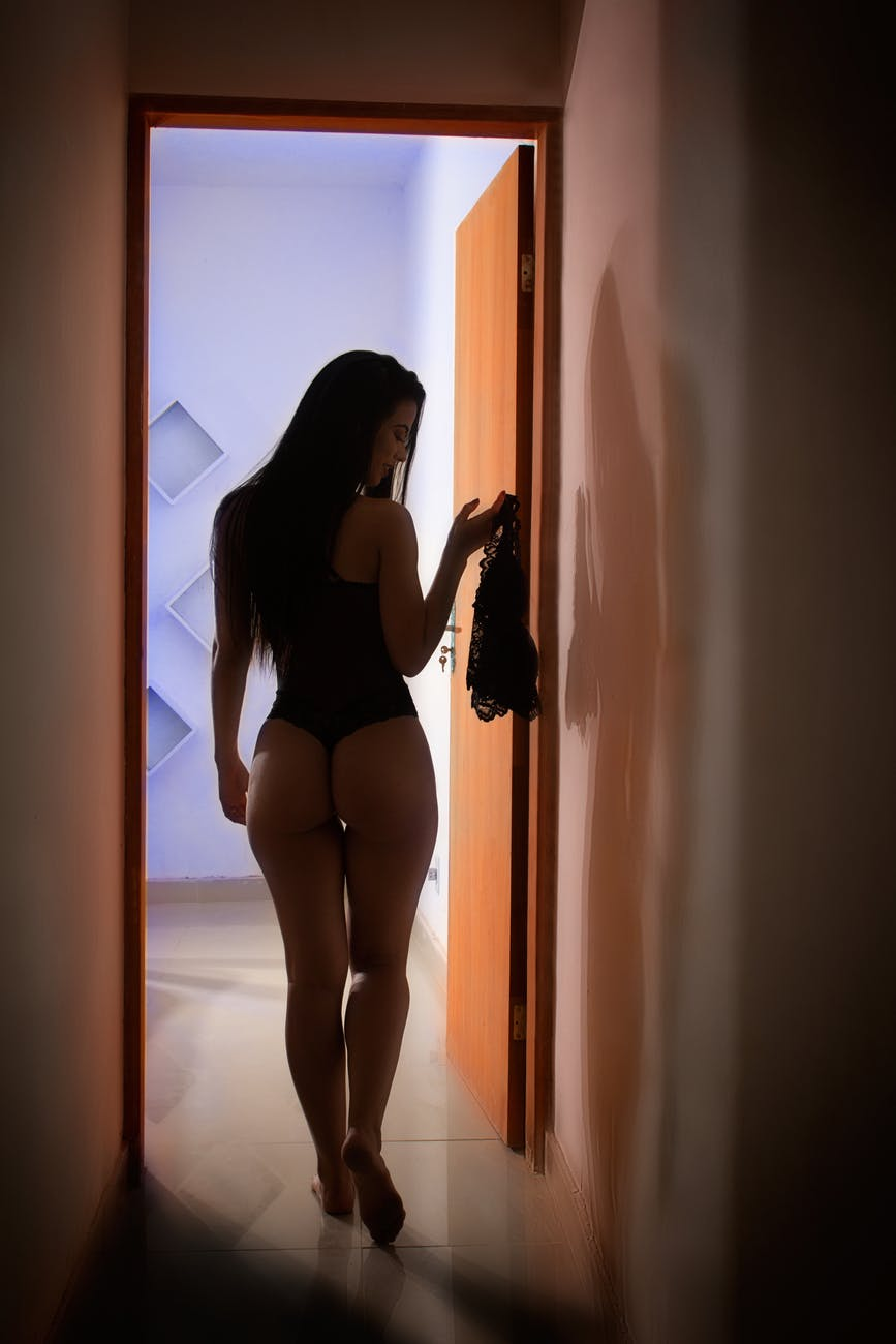 woman standing beside door inside room